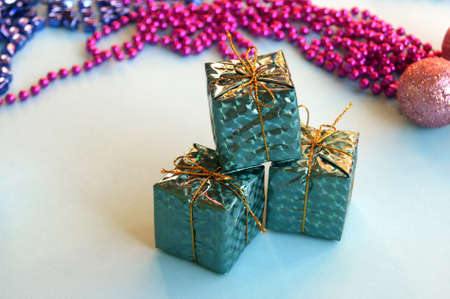 Christmas decoration for the Christmas tree in the form of small shiny gifts on a blue background.