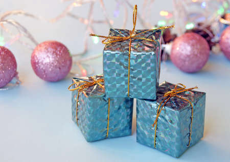 Christmas decoration for the Christmas tree in the form of small shiny gifts and balls on a blue background.