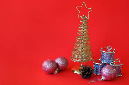 Golden metal Christmas tree with a star on top, red background. Stockfoto