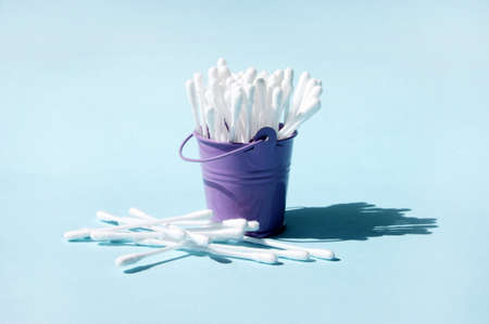 A lot of clean ear sticks in a miniature metal purple bucket. Cotton buds for cleaning ears. Body care.