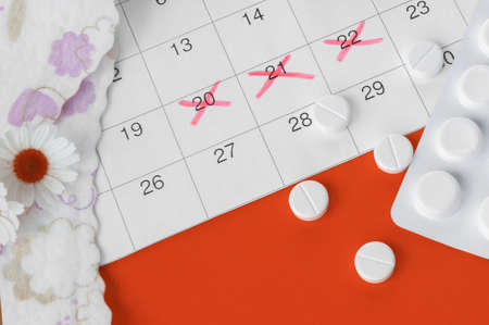Menstrual pads and tampons on menstruation period calendar with chamomiles on red background. The concept of female health, personal hygiene during critical days.