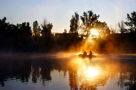 Two fisherman in a boat silhouette. Early morning sunrise, boating on the lake in the sunlight. Sunrise over the lake.
