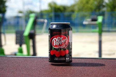 KHARKOV, UKRAINE - JUNE 12, 2020: A metal bottle of Dr Pepper drink on the background of a street sports ground. Blurred background.