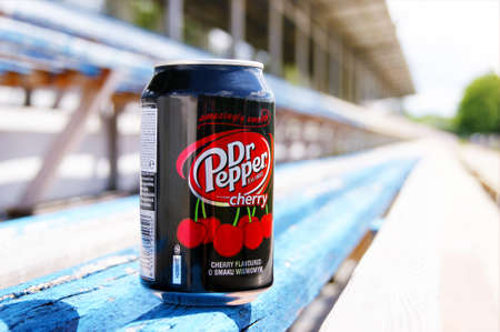 KHARKOV, UKRAINE - JUNE 12, 2020: A metal bottle of Dr. Pepper drink stands on a wooden bench in a small stadium. Blurred background.