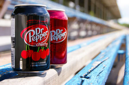 KHARKOV, UKRAINE - JUNE 12, 2020: A metal bottles of Dr. Pepper drink stands on a wooden bench in a small stadium. Blurred background.