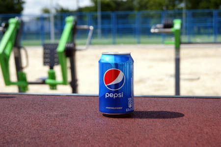 KHARKOV, UKRAINE - JUNE 12, 2020: A metal bottle of Pepsi drink on the background of a street sports ground. Blurred background.