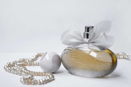 Perfume bottle with pearl on light background. Perfumery, cosmetics, fragrance collection.