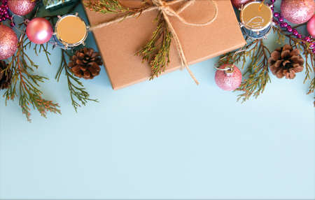 Christmas gift box, decoration and fir tree branch on light blue background. Top view with copy space Stock Photo