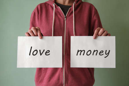 A young man holds a piece of paper with the words LOVE and MONEY. Choice concept. Money or love concept. Family or career choice.