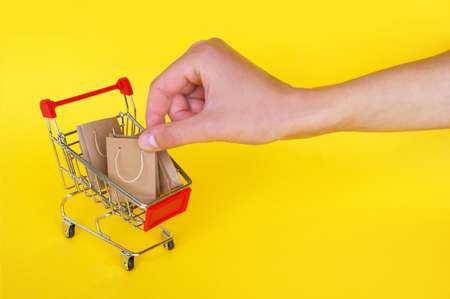 Mini cart and female hand with small craft bags on yellow background. The concept of shopping in stores and on the Internet.
