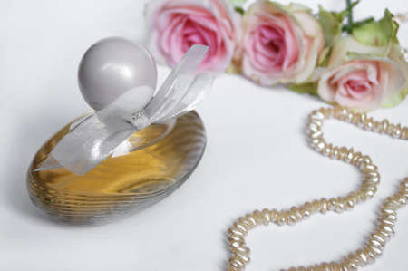 Perfume bottle with rose and pearls on a light background. Perfumery, cosmetics, fragrance collection.