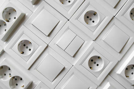 Many European outlets and switches are located next to each other. Background. Repair and wiring concept.