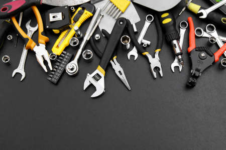 Many different tools for repair work on a black background with copy space for text. Repair and construction concept.