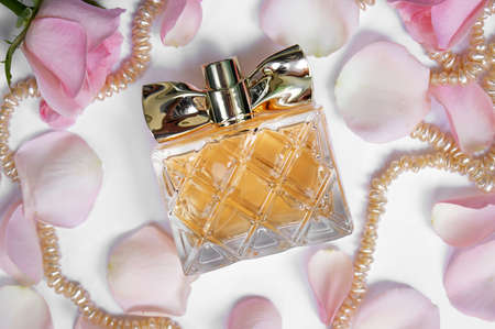 Perfume bottle with rose petals and pearls on a light background. Perfumery, cosmetics, fragrance collection.
