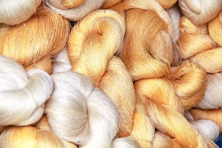 The roll of golden and white silk fiber for fabric material