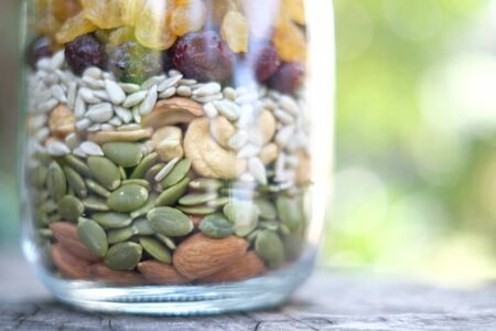 The mixed nuts in clear glass container is on the table with green background. Healthy food are contain in clear glass bottle