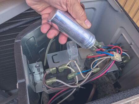 Air conditioner repair by technician. The technician replace the capacity run of airconditionaer