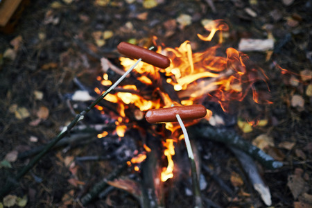sausages on sticks over a fire