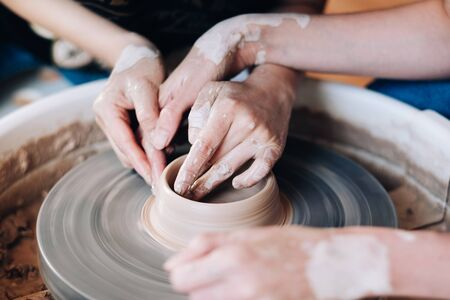 Woman potter teaching the art of pot making in pottery workshop. Stock Photo