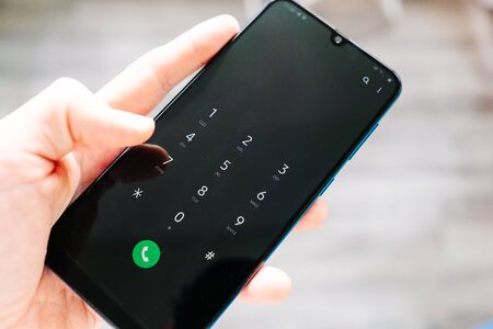smartphone male hand with call number on screen. view from above