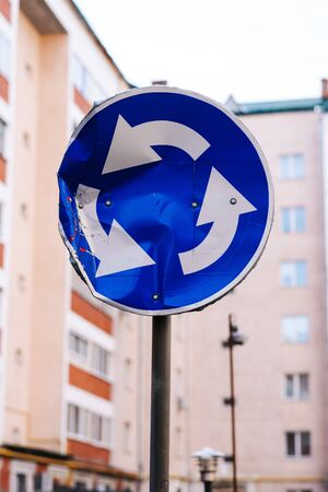 rumpled round metallic blue road traffic circle sign on sky and yard background Stock Photo