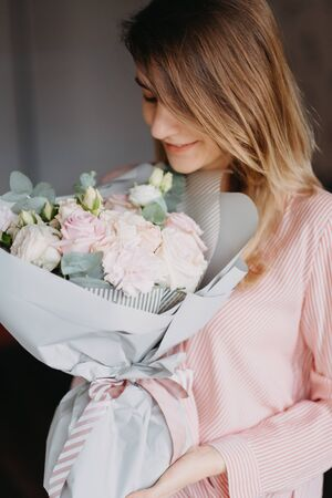 girl with a bouquet of flowers in her hands blonde hair in a pink shirt and black jeans