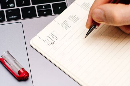 male hand encircles date 12 (twelve) in the diary calendar. on a laptop with a red pen 스톡 콘텐츠
