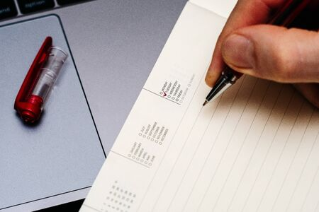 male hand encircles day of the week Tuesday in the diary calendar. on a laptop with a red pen