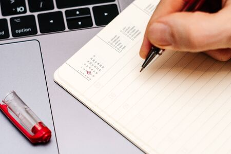 male hand encircles date 10 (ten) in the diary calendar. on a laptop with a red pen