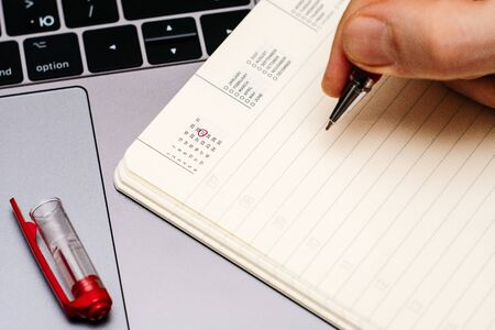 male hand encircles date 27 (twenty seven) in the diary calendar. on a laptop with a red pen