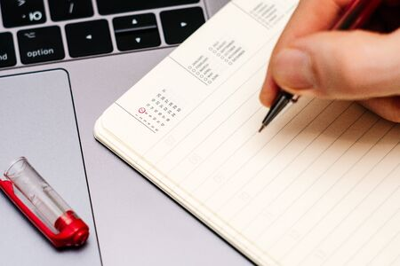 male hand encircles date 7 (seven) in the diary calendar. on a laptop with a red pen