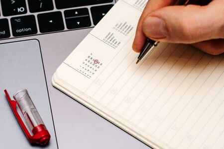 male hand encircles date 28 (twenty seven) in the diary calendar. on a laptop with a red pen