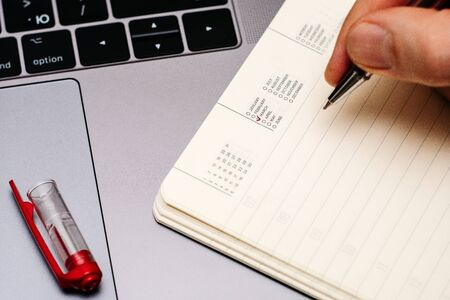 male hand encircles date month March in the diary calendar. on a laptop with a red pen