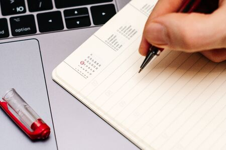 male hand encircles date 13 (thirteen) in the diary calendar. on a laptop with a red pen