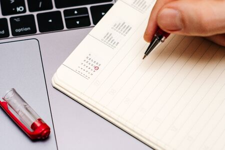 male hand encircles date 24 (twenty four) in the diary calendar. on a laptop with a red pen 스톡 콘텐츠