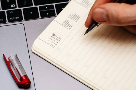 male hand encircles date 25 (twenty five) in the diary calendar. on a laptop with a red pen