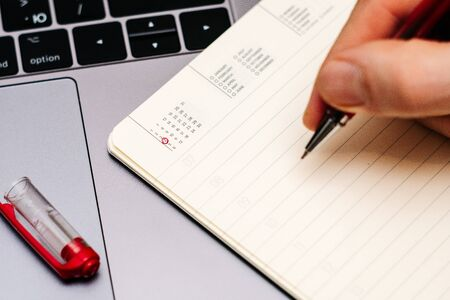 male hand encircles date 4 (four) in the diary calendar. on a laptop with a red pen