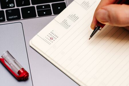 male hand encircles date 16 (sixteen) in the diary calendar. on a laptop with a red pen