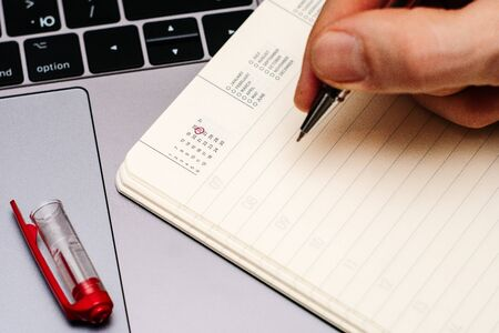 male hand encircles date 26 (twenty six) in the diary calendar. on a laptop with a red pen 스톡 콘텐츠