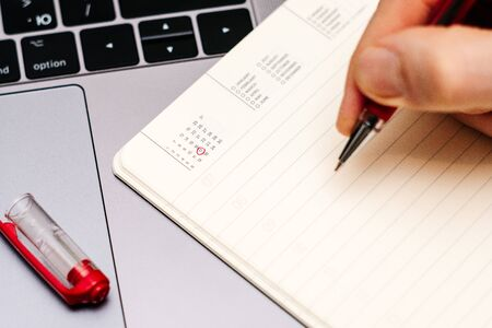 male hand encircles date 17 (sixteen) in the diary calendar. on a laptop with a red pen