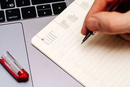 male hand encircles date 1 (one) in the diary calendar. on a laptop with a red pen 스톡 콘텐츠