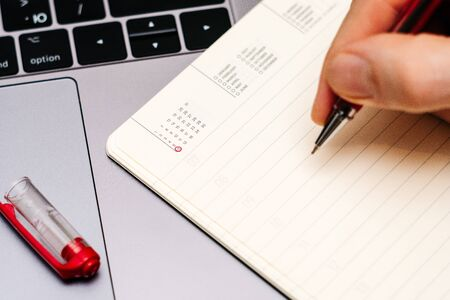 male hand encircles date 6 (six) in the diary calendar. on a laptop with a red pen