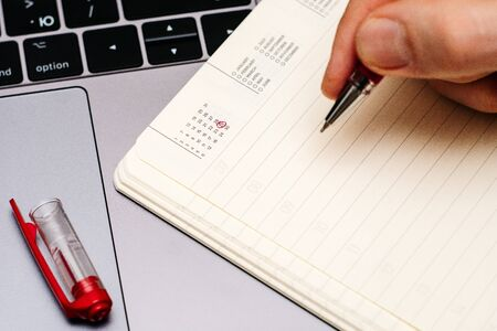 male hand encircles date 29 (twenty nine) in the diary calendar. on a laptop with a red pen