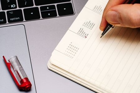 male hand encircles date month June in the diary calendar. on a laptop with a red pen