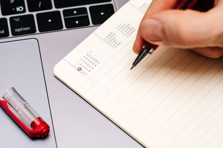 male hand encircles date 3 (three) in the diary calendar. on a laptop with a red pen