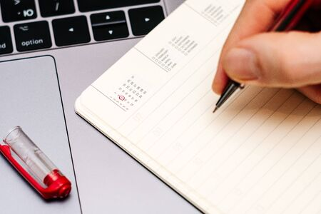 male hand encircles date 9 (nine) in the diary calendar. on a laptop with a red pen