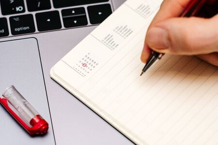 male hand encircles date 15 (fifteen) in the diary calendar. on a laptop with a red pen