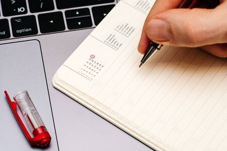 male hand encircles date 31 (thirty-one) in the diary calendar. on a laptop with a red pen 스톡 콘텐츠