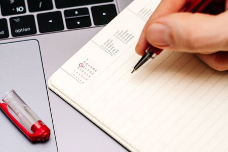 male hand encircles date 19 (nineteen) in the diary calendar. on a laptop with a red pen