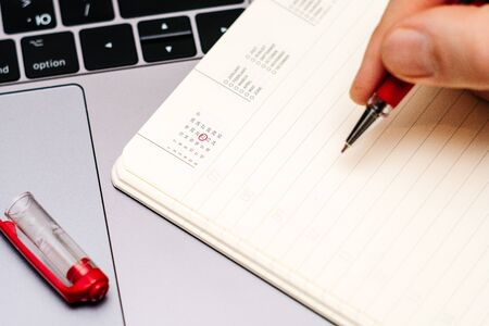male hand encircles date 2 (twenty two) in the diary calendar. on a laptop with a red pen